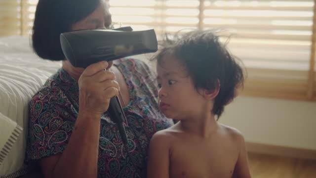 おばあちゃんは家で男の子をドレスアップ。 - くつろぐ点の映像素材/bロール