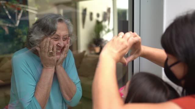 vídeos de stock, filmes e b-roll de avó cumprimentando filha e neta pela janela durante quarentena - usando máscara facial - adulto maduro