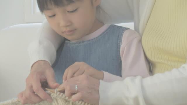 grandmother help granddaughter knit - 祖母点の映像素材/bロール