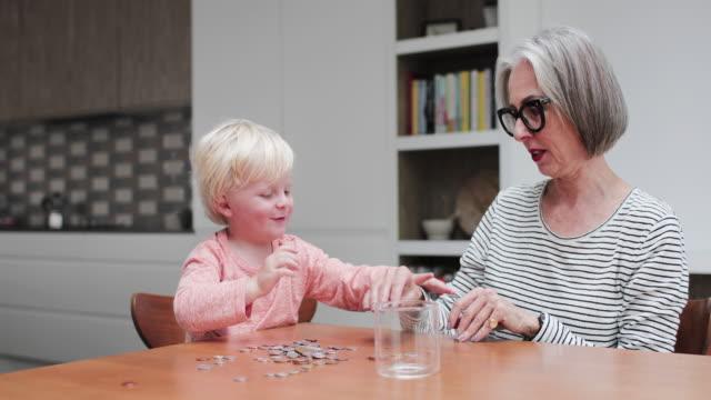grandmother helping grandchild count pocket money - 生後18ヶ月から23ヶ月点の映像素材/bロール