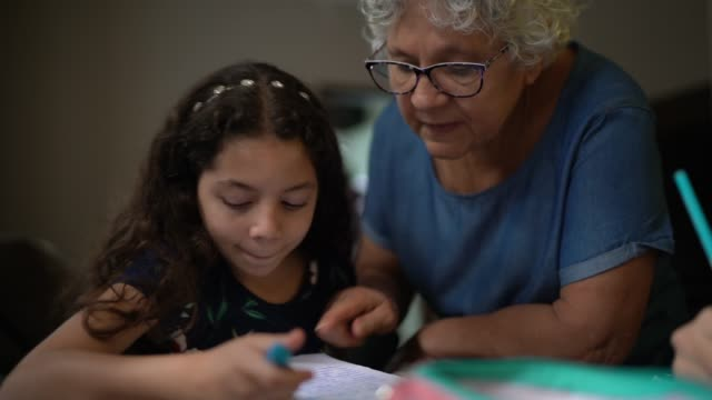 grandmother helping granddaughter with homework while they studying at home - granddaughter stock videos & royalty-free footage
