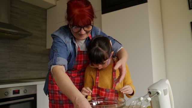 großmutter hilft ihrer enkelin, teig zu machen - backen stock-videos und b-roll-filmmaterial