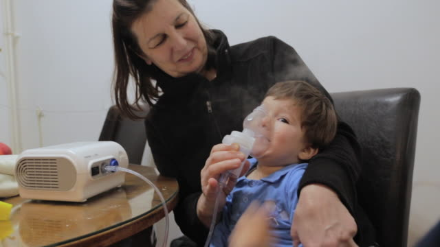 farmor hjälpa lille pojke att använda nebulisator för astma och luftvägssjukdomar hemma. begreppet hem behandling. inhalationsterapi - syrgasmask bildbanksvideor och videomaterial från bakom kulisserna