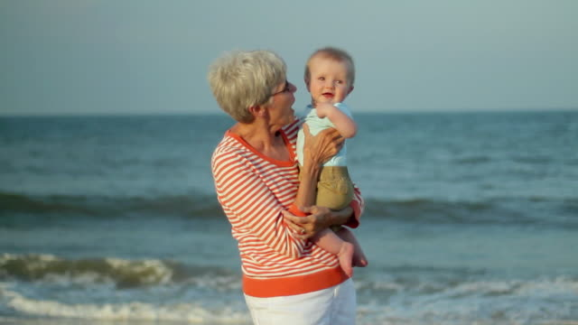 MS Grandmother holding baby boy (2-5 months) on beach / Millville, Delaware, USA