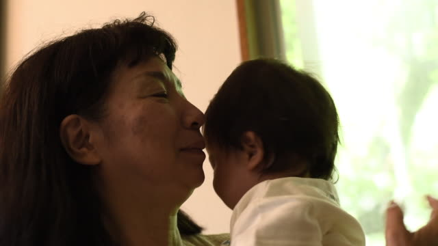 grandmother holding her grand son - senior women stock videos & royalty-free footage