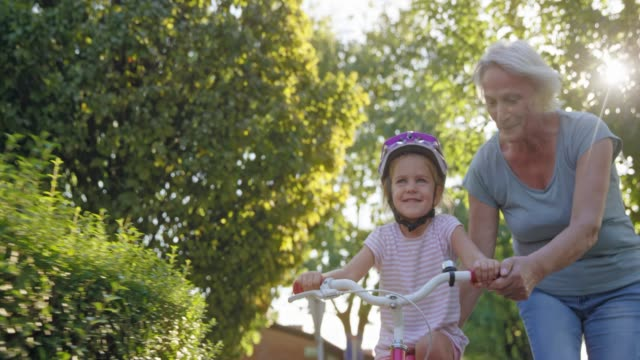 slo mo ds grandmother holding the seat of the bike her granddaughter is learning to ride in sunshine - terza età video stock e b–roll