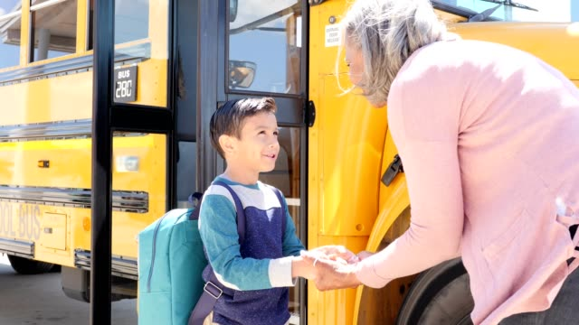 grandmother holds her young grandson's hand as he prepares to board school bus - saying goodbye stock videos & royalty-free footage
