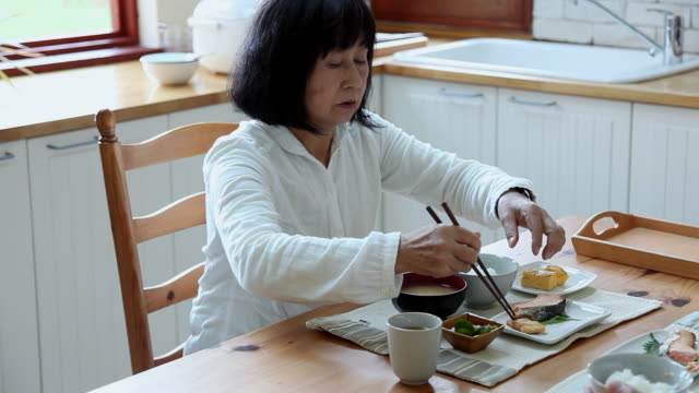 ms grandmother is eating breakfast in kitchen / fujikawaguchiko, yamanashi, japan - 食事点の映像素材/bロール
