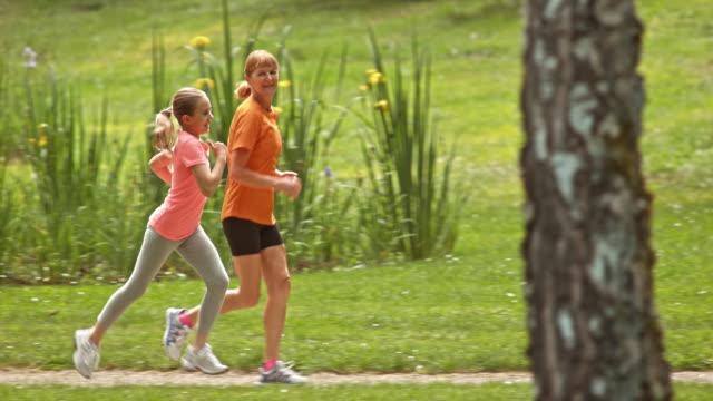 vídeos de stock, filmes e b-roll de slo mo t avó jogging no parque com neta - camiseta