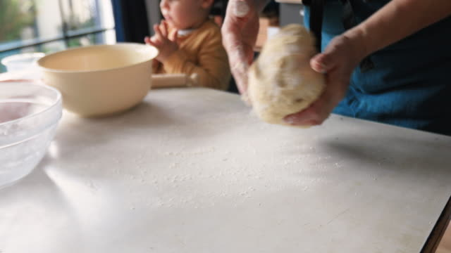 vídeos de stock e filmes b-roll de grandmother kneading yeast dough - pão