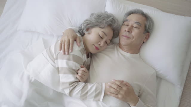a grandmother lies in a grandfather's arms at home - 韓国人点の映像素材/bロール