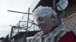 A Grandmother Listening to Music with a Set of Headphones and a Phone.