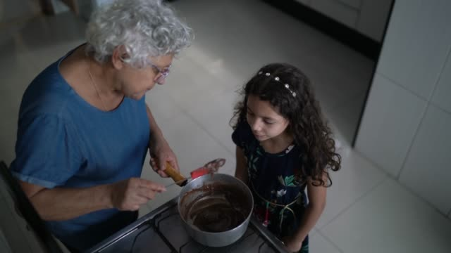 grandmother making chocolate with granddaughter at home - granddaughter stock videos & royalty-free footage