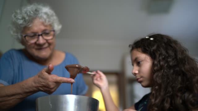 vídeos de stock, filmes e b-roll de avó fazendo chocolate com neta em casa - preparing food