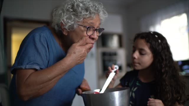 grandmother making chocolate with granddaughter at home - baking stock videos & royalty-free footage