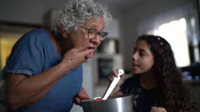nonna che fa il cioccolato con la nipote a casa - nonna video stock e b–roll