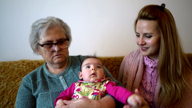 Grandmother, mother and baby at home