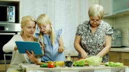 Grandmother, mother and granddaughter cook together a salad in the kitchen. Enjoy a tablet, have a good time