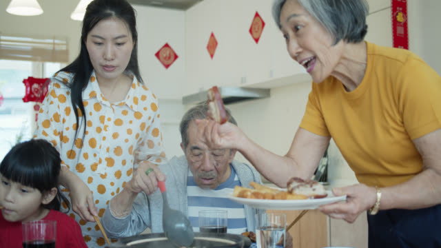 grandmother offering food to family at chinese new year - chinese new year stock videos & royalty-free footage