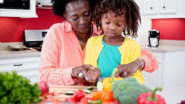 Grandmother or mother and daughter cooking together in home kitchen.