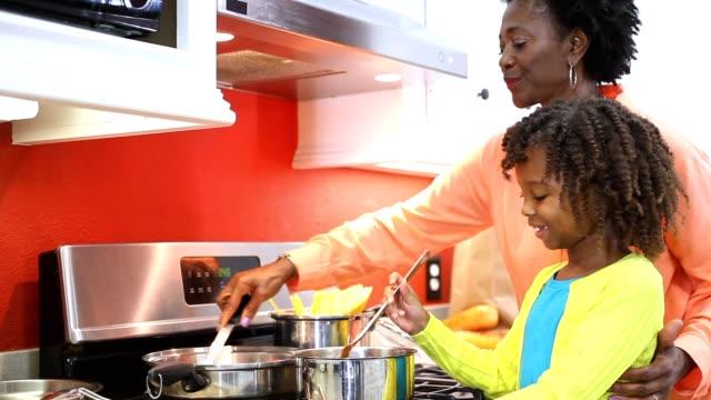 Oma of moeder en dochter samen koken in eigen keuken.