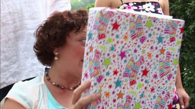 Grandmother passing gift to granddaughter at birthday party / New Jersey