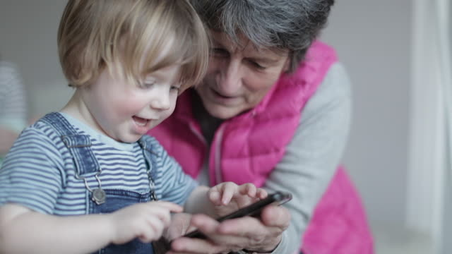 grandmother playing on smartphone with laughing grandson - enkelin stock-videos und b-roll-filmmaterial