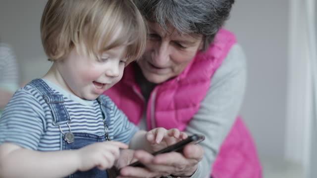 vídeos y material grabado en eventos de stock de grandmother playing on smartphone with laughing grandson - abuela
