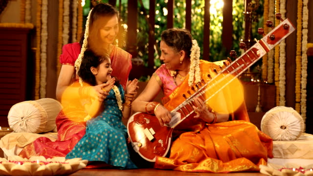 ms grandmother playing sitar while her granddaughter and daughter in law clapping hands during pongal festival / new delhi, delhi, india - celebration stock videos & royalty-free footage