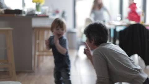 vídeos y material grabado en eventos de stock de grandmother playing with grandson in kitchen - nieto