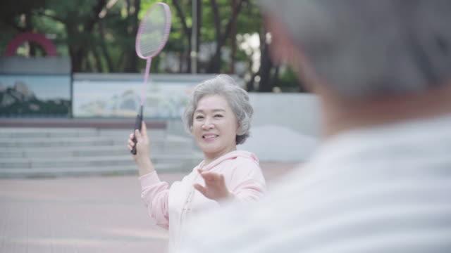 vídeos de stock, filmes e b-roll de a grandmother prepares to receive a shuttlecock at park - badmínton esporte