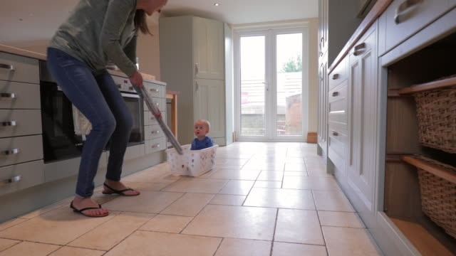 grandmother pulling grandson across the kitchen in a washing basket - laundry basket stock videos and b-roll footage