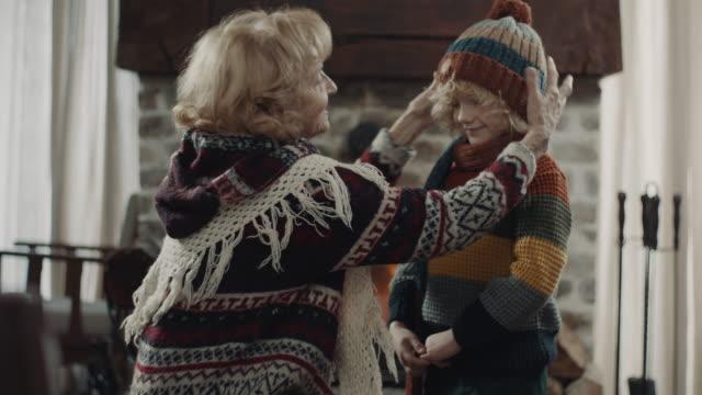 vídeos y material grabado en eventos de stock de abuela poniendo gorra de invierno en la cabeza del nieto - jersey de cuello alto