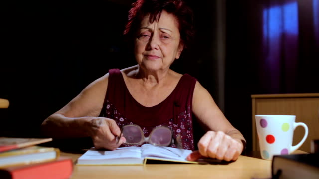 grandmother reading a book and crying - old lightbulb stock videos and b-roll footage
