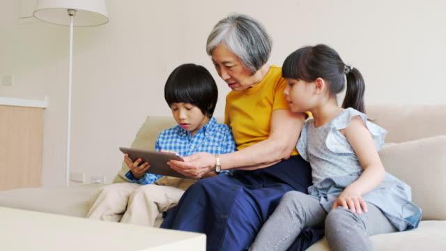 vídeos y material grabado en eventos de stock de abuela leyendo a los niños en un hogar en taiwán - chino oriental