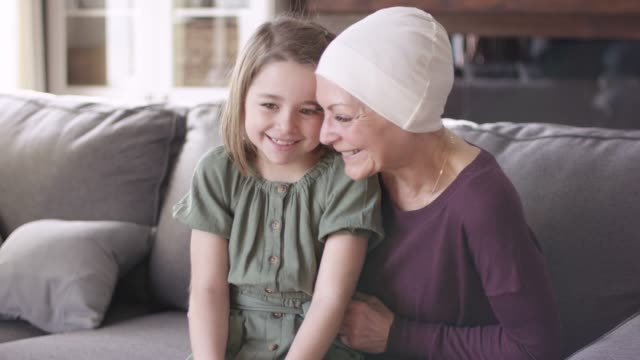 a grandmother recovering from cancer snuggles with her granddaughter on the couch. - cancer illness stock videos & royalty-free footage