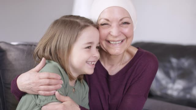 a grandmother recovering from cancer snuggles with her granddaughter on the couch. - affectionate stock videos & royalty-free footage