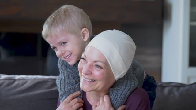 una nonna che si riprende dal cancro si coccola con suo nipote sul divano. - nonna video stock e b–roll