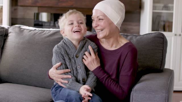 a grandmother recovering from cancer snuggles with her grandson on the couch. - survival stock videos & royalty-free footage