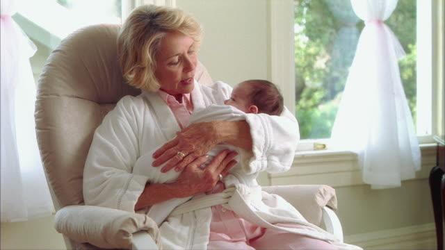 vídeos y material grabado en eventos de stock de ms grandmother rocking newborn baby girl (0-1 months) in rocking recliner / tampa, florida, usa - 0 1 mes