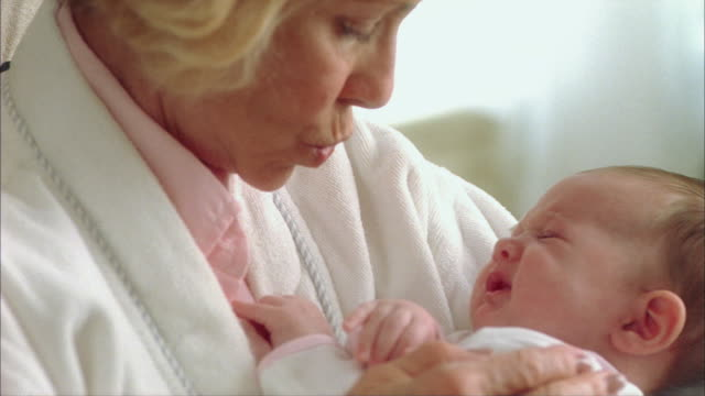 vidéos et rushes de cu grandmother rocking sleepy newborn baby (0-1 months) / tampa, florida, usa - grand mère