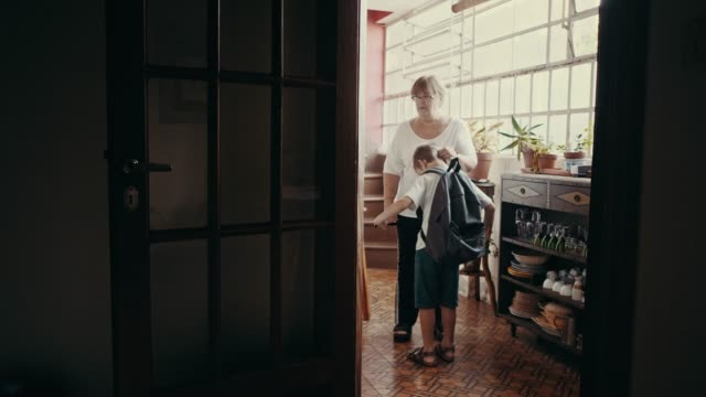 grandmother sends grandchild to school by helping to put on the schoolbag (slow motion) - doorway stock videos & royalty-free footage