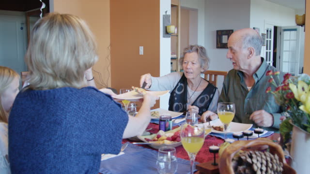 grandmother serves food during multi-generational meal - serving food and drinks stock videos and b-roll footage