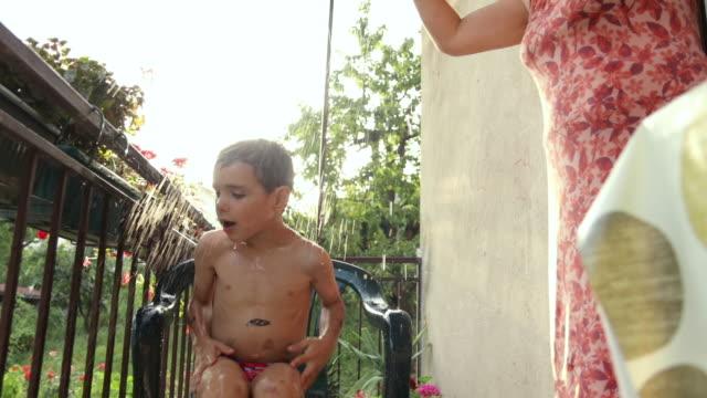 vídeos y material grabado en eventos de stock de abuela duchando a su pequeño en el balcón con ducha improvisada durante la puesta del sol - bronceado