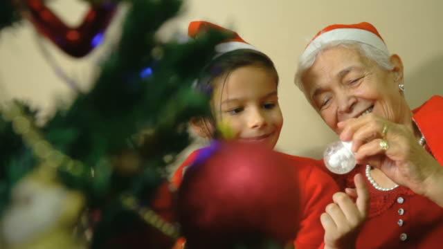 grandmother showing snow globe to grandson in santa hat - storyteller stock videos & royalty-free footage