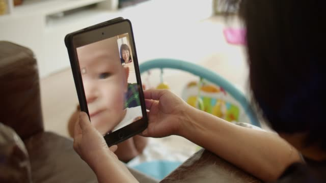 grandmother talks to grandchild on tablet - distant stock videos & royalty-free footage