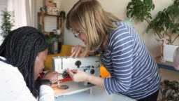 Grandmother teaching granddaughter and daughter-in-law how to use sewing machine