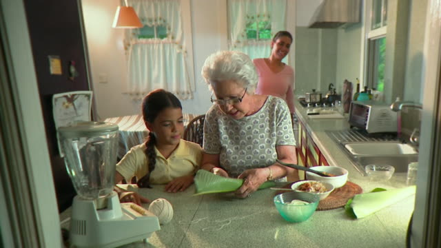 vidéos et rushes de ms grandmother teaching granddaughter (6-7) how to cook tamale dish on kitchen table, panama city, panama  - grand mère