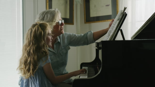 vídeos de stock e filmes b-roll de grandmother teaching granddaughter to play piano / pleasant grove, utah, united states - pianista