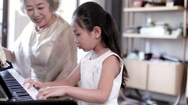grandmother teaching granddaughter to play the piano,4k - high society stock videos & royalty-free footage